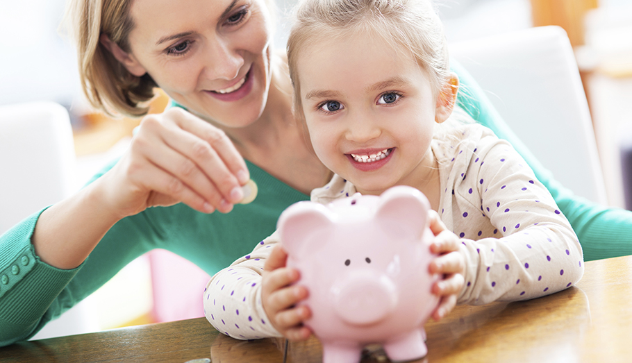 Mother and young daughter putting a coin into a piggy bank.