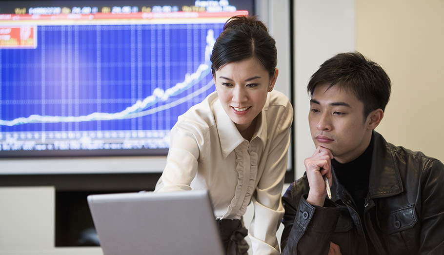 Business woman showing investment growth to a young man on the computer