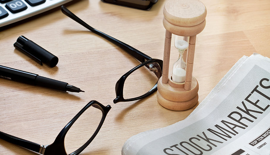 Stock market report with glasses beside it..