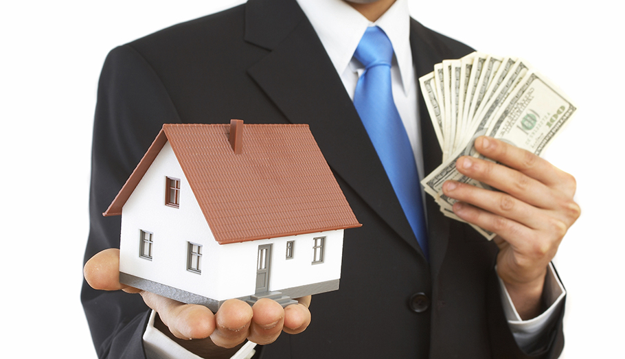 Man holding a model house and a hand full of money.